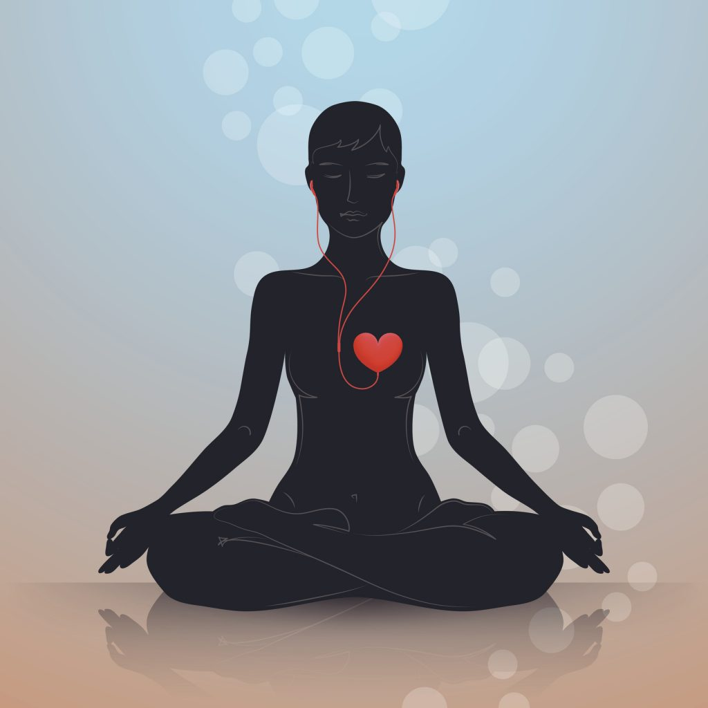 woman sitting in lotus position, listening to headphones connected to heart shape