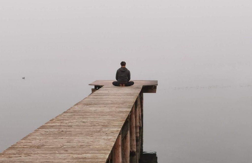 man on lake dock